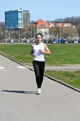 Athletic young male running around the city