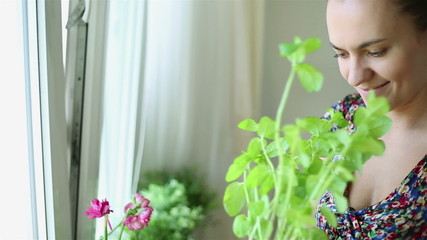 Woman smells the aroma herbs in her kitchen, steadicam shot