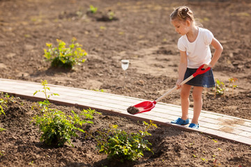 Cute Little girl gardening in summer day