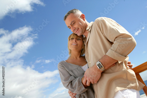 Couple stood on a balcony by the sea