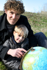Father and son looking at a globe