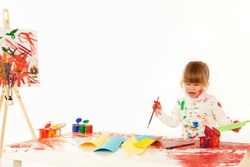 pretty baby girl painting in white studio