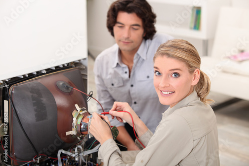 Woman fixing a television set