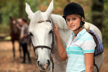 Girl stroking white horse