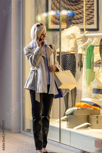 Young woman window shopping evening city