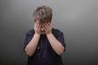 Trauriger Junge mit Hand vor dem Gesicht