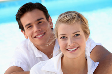 Smiling young couple with a blue sky background