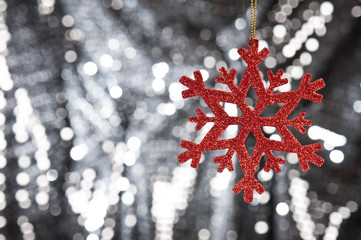 Red snow flake on a silver glitter background