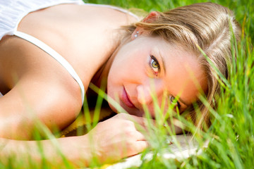 young beautiful girl lie in grass