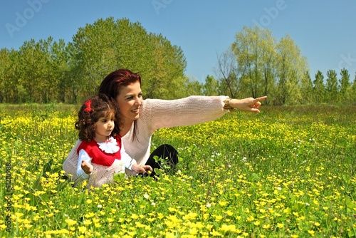 Mother showing something her daughter at the meadow