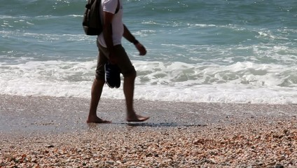 A young man walks along the beach barefooted