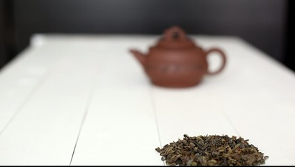 Chinese teapot and green tea pile on white  table