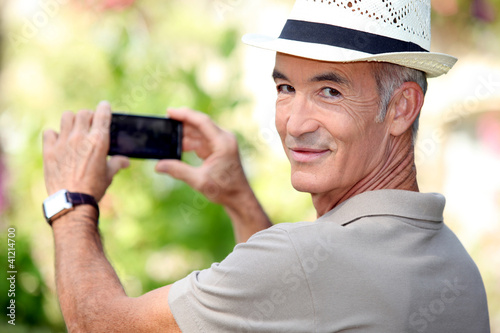 Middle -aged man taking photo whilst wearing straw hat