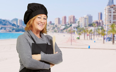 portrait of cook middle aged woman smiling near the beach