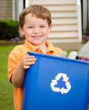 Recycling concept with young child carrying recycling bin