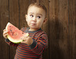 portrait of a handsome kid holding a watermelon and tasting agai