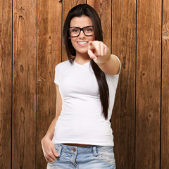 portrait of young woman pointing with finger against a wooden wa