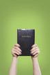 Holding the Bible High on Green