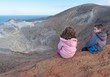Girl and boy sitting on rim of volcano crater near Sicily