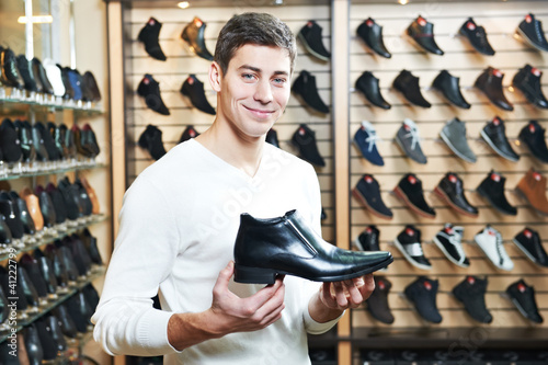 Young man at choosing shoe in clothes store - 41222799