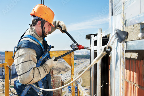 Worker builders at facade tile installation - 41222963