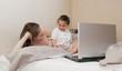 Fille et sa mère dans le lit devant l'ordinateur