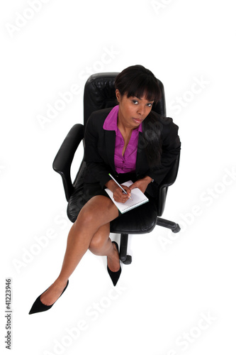 Businesswoman writing in a notepad