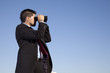 Businessman looking though binoculars
