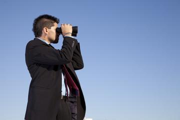 Businessman looking though binoculars