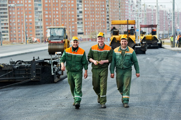 three asphalt workers at road