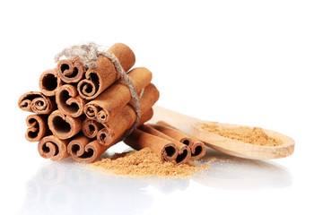 Cinnamon sticks and powder in wooden spoon isolated on white