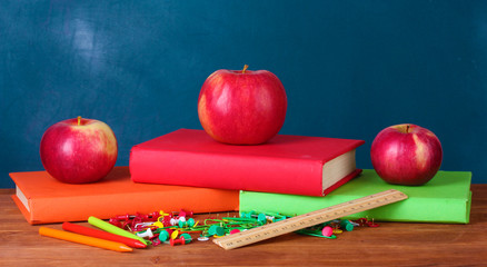 Composition of books, stationery and an apples