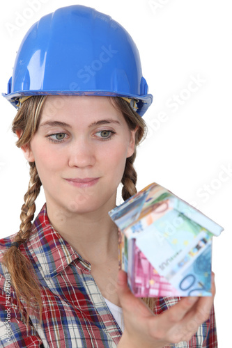Female builder holding house made from bank notes