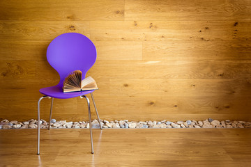 Purple chair with opened book next wooden wall / modern interior