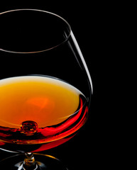 cognac in glass isolated on black background