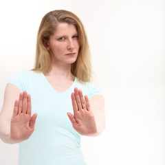 Girl with a serious look holding out her hand signaling stop