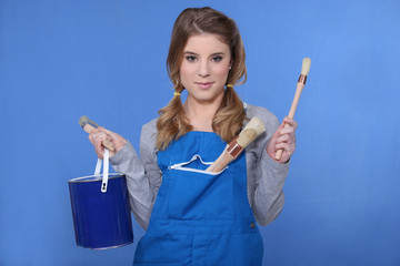 Woman holding paint brush and paint pot