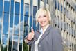 Hübsche Geschäftsfrau vor Geschäftshaus lächelt Daumen hoch