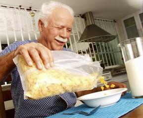 Abuelo desayunando cereal en casa.