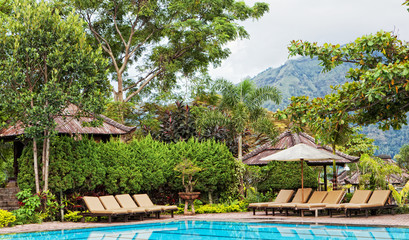 Chaise lounges at pool in hotel in tropics