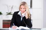 geschäftsfrau macht sich notizen beim telefonieren