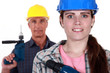 Man and woman holding power drills
