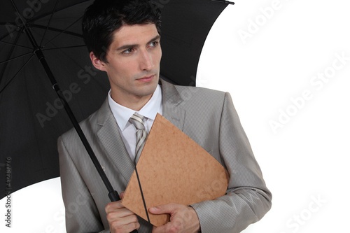 A businessman holding an umbrella.