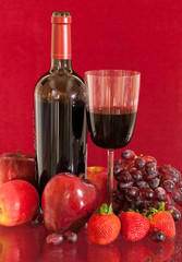 Red wine bottle and fruit with glass