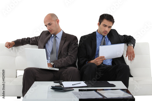 Two businessman sat on sofa checking through document