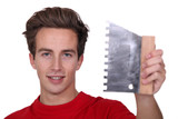 Young man with a tile adhesive comb