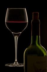 Rotwein im Glas mit Flasche