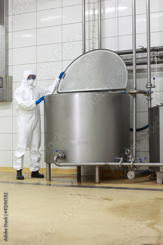 technician in uniform closing  industrial process tank