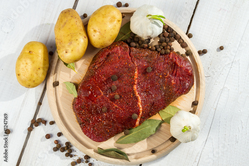 Raw steak spiced with herbs ready for baking
