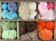 many colorful yarns in wooden box